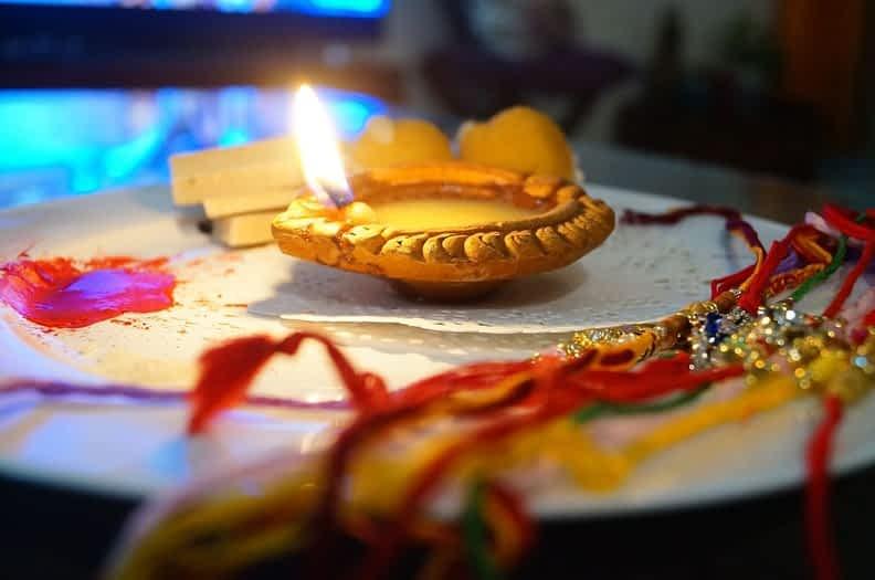 Diya with a decorated plate of rakhi